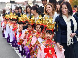 母親らと手をつなぎ、色鮮やかな衣装で商店街を練り歩く子どもたち