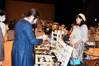 手作りのアクセサリーを販売する女性(右)