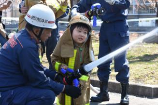 消防体験でホースを持ち放水する子ども