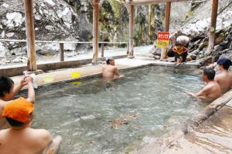 今季の営業を開始した温泉に漬かり、眺めを楽しむ観光客