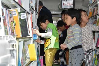 「新・あおぞら号」で楽しそうに本を選ぶ一方井保育所の園児たち