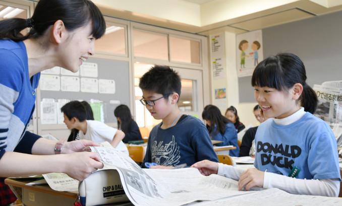 生き生きとした表情で岩手日報を読む福岡小の6年生=8日、二戸市福岡