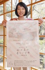初開催の「山の上の手しごと市」のポスターを掲げ、来場を呼び掛ける事務局の高村麻里さん