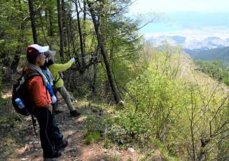 新緑や市内の景色を楽しみながら歩を進める登山者