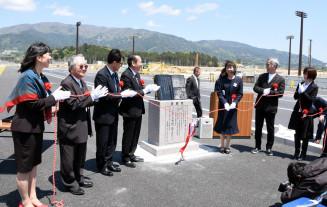 記念碑を除幕する浅沼ミキ子代表(右から3人目)ら