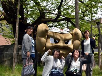 岩手の応援ポケモンに決まった「イシツブテ」。石割桜の前で写真撮影に応じた=14日、盛岡市内丸