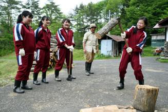 徳谷真樹さん(右から2人目)の指導でまきを割る生徒