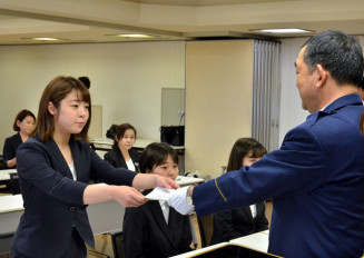 吉田良夫生活安全部長から少年サポート隊の委嘱書を受け取る大学生