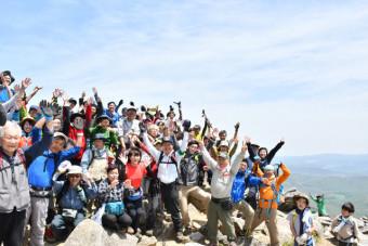 登頂の喜びを分かち合い万歳三唱する人たち