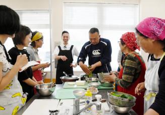寺沢勇人さん(左から4人目)から手ほどきを受け料理に挑戦する参加者