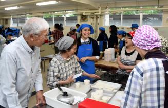 会話を弾ませながら一緒に調理する花巻農高の生徒と被災者