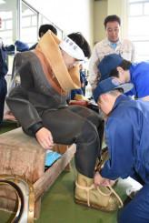 種市高の海洋開発科の生徒に「南部もぐり」の装備を装着してもらう衣笠中の生徒(左)