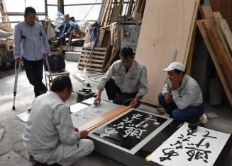 震災の教訓を記す祈念碑の加工が始まり、作業を見守る木村正明さん(左)