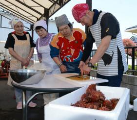 山下聖人店長(右から2人目)からホヤのさばき方を学ぶ参加者