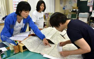 地図を広げて児童の自宅を確認する山王小の教員ら=盛岡市小杉山
