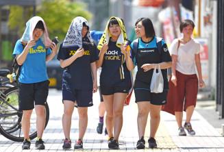 強い日差しが照りつける中、タオルで暑さをしのいで歩く高校生ら=26日、一関市大町