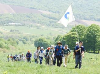 牧野を一歩ずつ進み、山頂を目指す登山隊