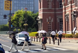 暑さを和らげるため日傘を差して歩く市民ら=27日午後2時20分ごろ、盛岡市中ノ橋通