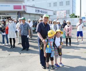 交差点で紺野功さん(手前)からスクールガードの注意点などについて説明を受ける講習会参加者