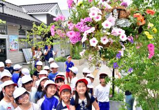 三陸鉄道宮古駅前に飾ったハンギングバスケットを見上げる児童
