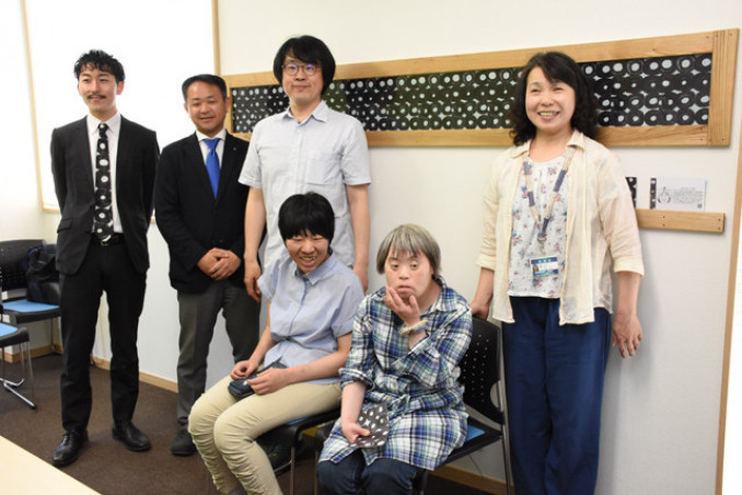 佐々木早苗さんの作品を前に喜ぶ(左から)松田文登副社長、笠井健社長、高橋南さん(手前左)、佐々木さん