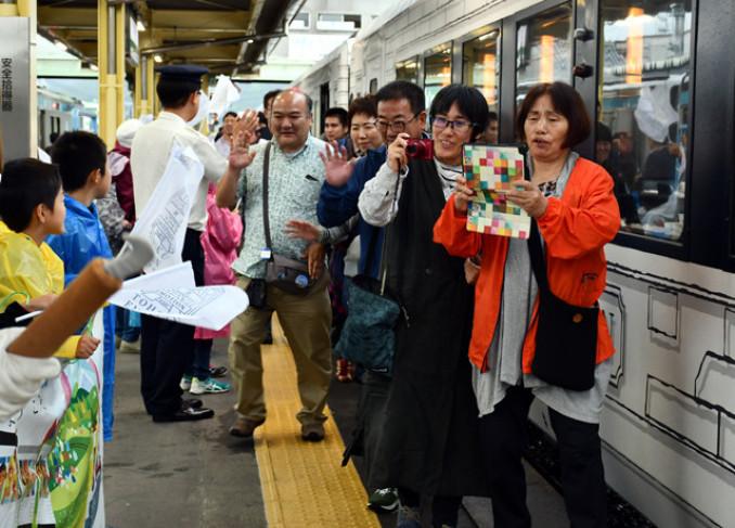 地元住民の歓迎を受け喜ぶ乗客