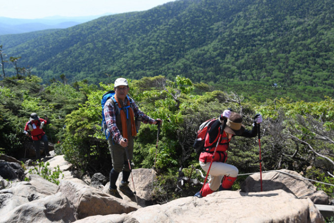 険しい岩場に注意して進む登山客