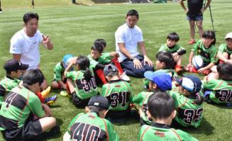 子どもたちにラグビーで大切な心構えを伝える広瀬俊朗さん(左奥)と五郎丸歩選手(中央奥)