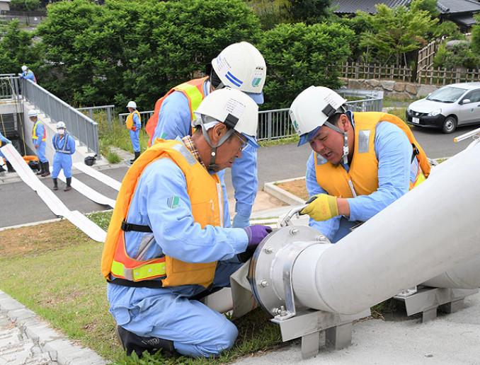 ホース設置の作業手順を確認する作業員