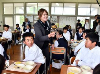写真を手に生徒へナミビア料理を説明する佐々木フレデリカさん(中央)
