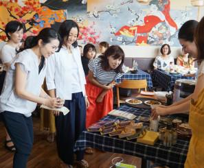 県産の海鮮丼や漬物などに興味を示す試食会の参加者=10日、ベトナム・ホーチミン市(白金運輸提供)