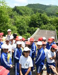 旧祭畤大橋が落橋した現場で当時の話を聴く厳美小の5年生=14日、一関市厳美町