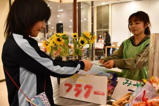 疑似通貨・ベスカを支払い、デパートに並べる商品を仕入れる児童(左)