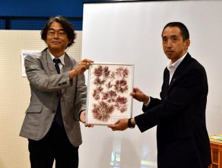 国立科学博物館で修復した海藻標本を佐々木茂人教育長に手渡す北山太樹研究主幹(左)
