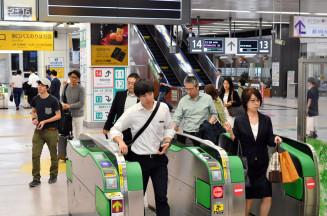 地震の影響で到着が遅れた新幹線から降り、改札を通る乗客=18日午後11時16分、盛岡市・JR盛岡駅