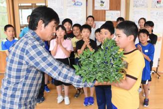 立花賢生部会長から修学旅行の訪問先などで配るリンドウを受け取る小山田佑真君(右)