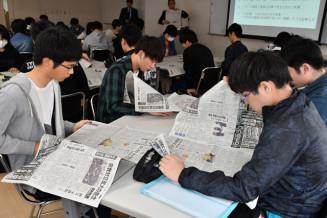 新聞の全ページに目を通し、気になる記事を探す盛岡情報ビジネス専門学校の学生