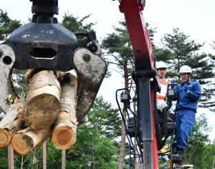林業機械の操縦を体験する下舘快さん(左)