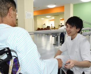 「新聞を読むようになり、伝える力、聞く力がついたと思う」と語り、患者に笑顔で接する荒沢隼さん