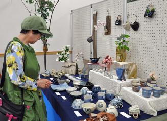 地元で作られた味わい深い陶器などを観賞する来場者