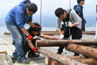 丸太を組み合わせ、いかだを作る参加者たち
