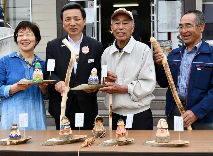つえとこまを手にほほ笑む(左から)高谷淳子さん、中村一郎社長、木藤古徳一郎さん、中戸鎖征夫さん
