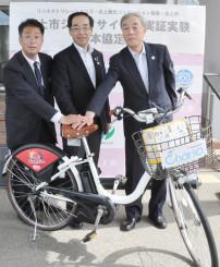 シェアサイクルの実証実験へ連携を誓う(左から)富樫建社長、高橋敏彦市長、八重樫守民会長
