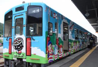 釜石駅のホームに入ったラグビージャージー姿のキャラクター35体が描かれたラッピング車両=25日、釜石市鈴子町