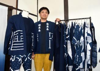 一関発のローカルウエアに「祭りを身にまとって」と呼び掛ける蜂谷淳平専務。左の衣服は上がはんてん、腹掛け、下はさっぱかま