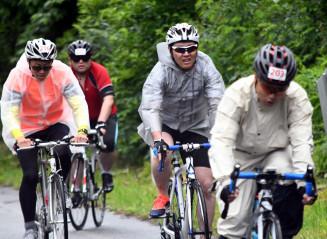 雨にぬれながら力強くペダルを踏む参加者