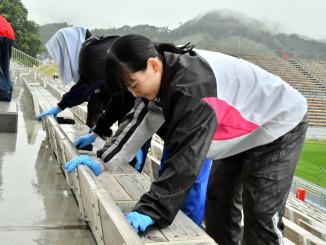 釜石鵜住居復興スタジアムの木製シートを清掃する地元高校生