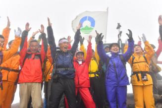 荒天により山頂セレモニーは中止となったが、有志が登頂成功を祝って万歳で互いをたたえた=1日午前11時45分、岩手山山頂