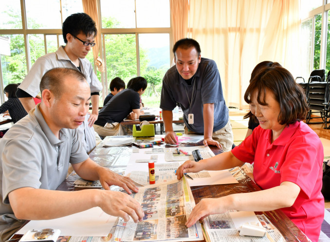 記事の切り抜きを選んで台紙に貼り付け、オリジナル新聞を製作する参加者