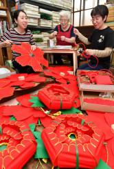 伝統さんさの花がさ作りを続ける高橋雅子社長(中央)。右は長女宗子さん、左は次女木村和子さん=7日、盛岡市肴町